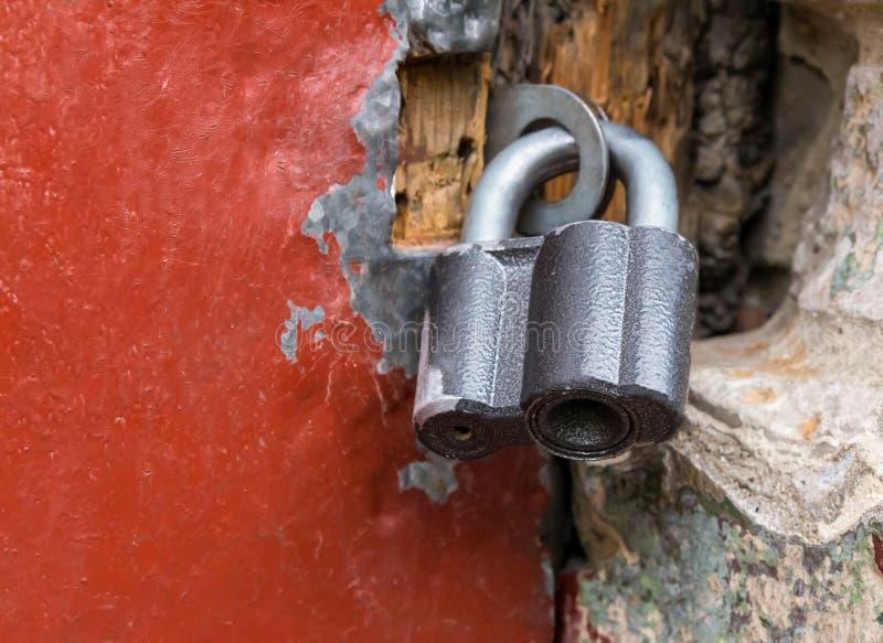 Trädörren som är destinerad med järn av röd färg, stängs med en stor hänglås arkivfoto