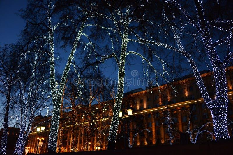 Träd i gatan av Moskva som dekoreras med girlander för nytt år arkivbilder