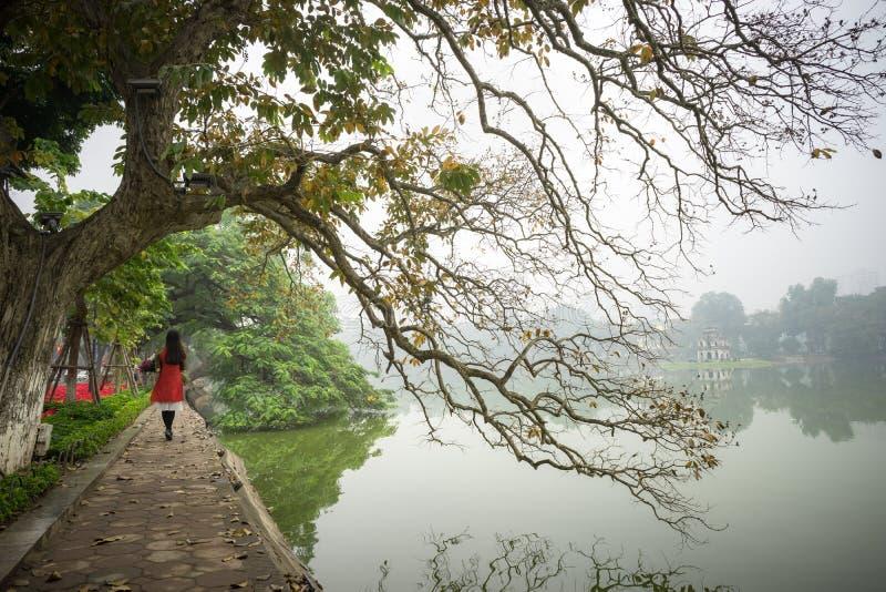 Träd i nedgångsäsong på Hoan Kiem sjön med den traditionella klänningen Ao Dai som för vietnamesiska flickakläder går vid sjön i  royaltyfri foto