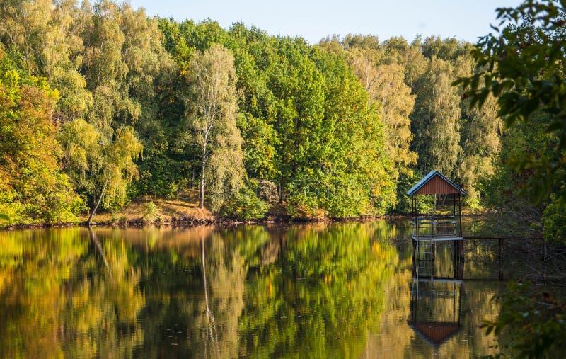 Träd reflekterade i floden och en liten gazebo på pir arkivbild
