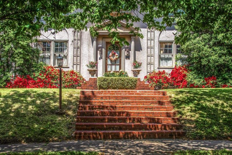 Träd skuggad fläckig trottoar och sluttad gräsmatta framme av det exklusiva stuckaturhuset med kransen och azaleor och härliga te royaltyfria foton