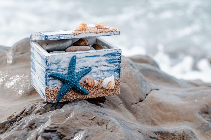 Trädekorativ bröstkorg med havsskal och blå stjärna på havskusten arkivfoton