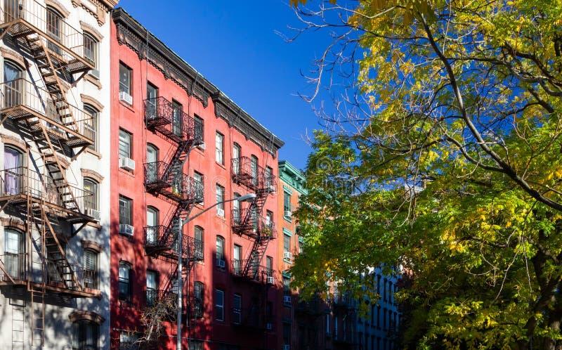Trädet fodrade gatan med gamla historiska hyreshusar i East Villagegrannskapen av New York City arkivbilder