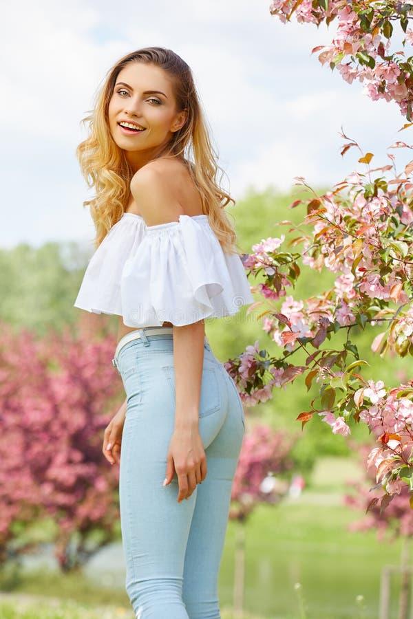 trädgård för kvinna på våren bland äppleblomningen royaltyfri bild