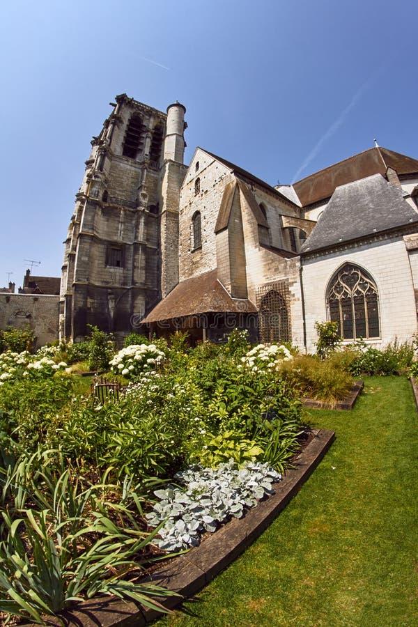 Trädgård med en medeltida kyrka arkivfoto