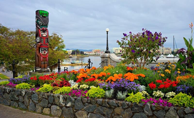 Trädgård och totem på bankerna av Victoria Inner Harbour, British Columbia, Kanada fotografering för bildbyråer