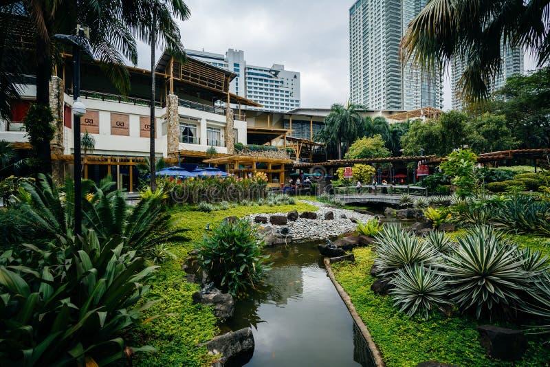 Trädgårdar och skyskrapor på grönt bälte parkerar, i Ayala, Makati som möts arkivfoton