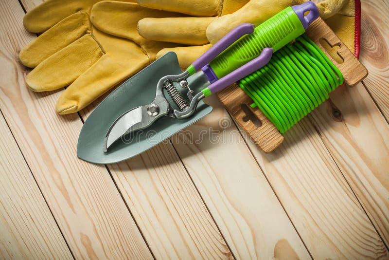 Trädgårdhjälpmedel räcker handskar för spadesekatörroupe på trä fotografering för bildbyråer