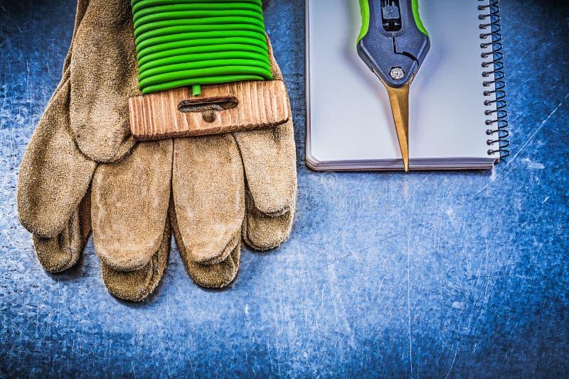 Trädgårds- arbetsbok för handskar för säkerhet för bandtrådpruner på metallisk backgr royaltyfri bild