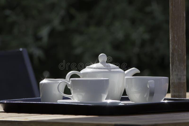 Trädgårds- eftermiddagtebjudning för sommar Den vita lerkärltekannan kuper arkivbild