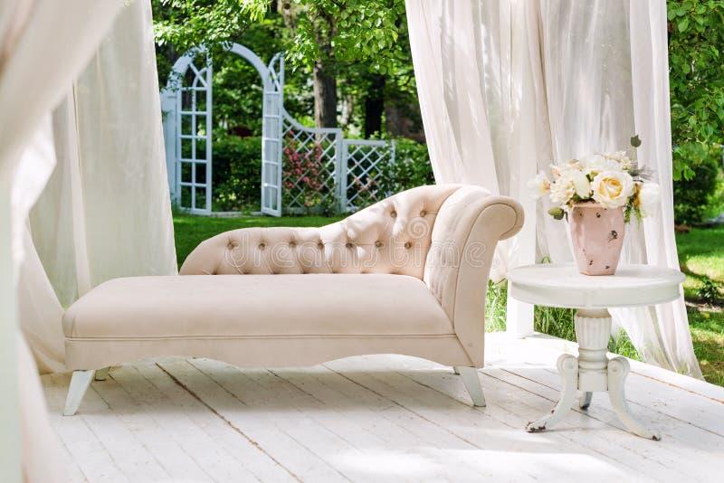 Trädgårds- gazebo för sommar med gardiner och soffan för avkoppling royaltyfri fotografi