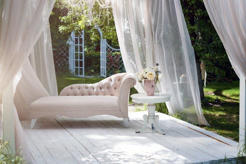 Trädgårds- gazebo för sommar med gardiner och soffan för avkoppling arkivbild