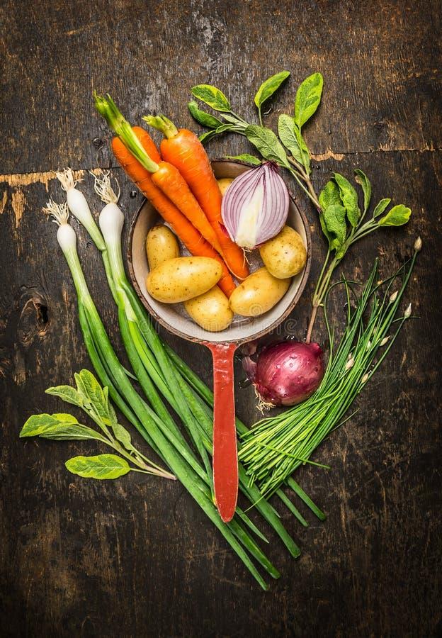 Trädgårds- grönsakingredienser i gammal matlagning lägger in på lantlig träbakgrund arkivfoton