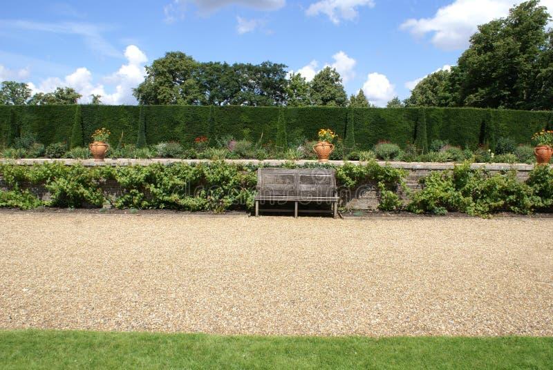 Trädgårds- grusbana med en träbänk och vaser arkivbild