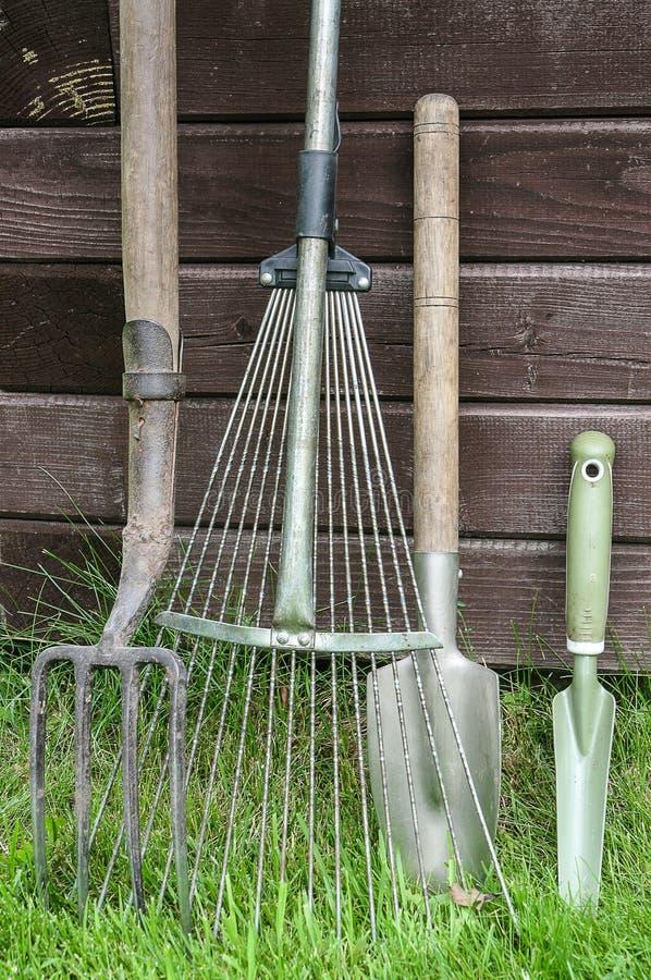 Trädgårds- hjälpmedel på gräs arkivbild