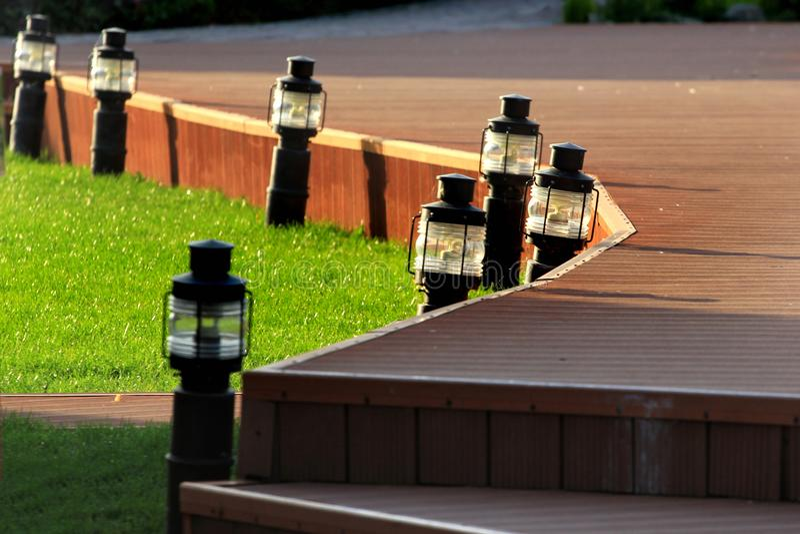 Trädgårds- lampor på en grön gräsmatta med den högstämda plast- vandringsledet royaltyfria foton