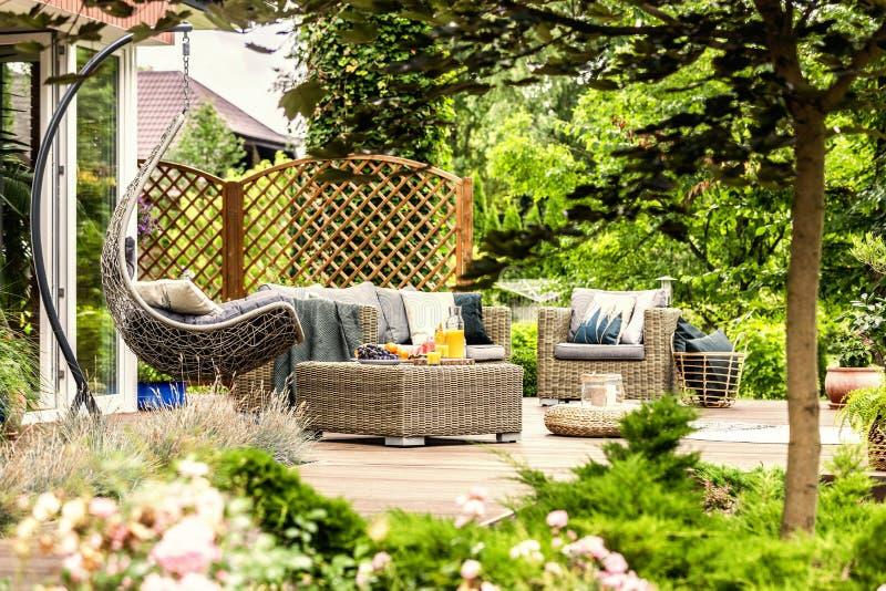 Trädgårds- möblemang för rotting och hängande stol på träterrass av H arkivfoto
