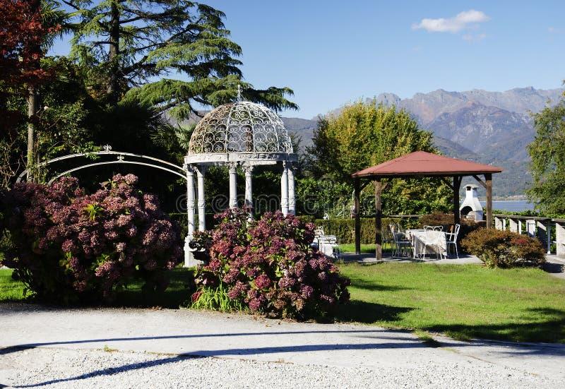 Trädgårds- paviljonger i ett litet parkerar på kust av sjön Maggiore i höst royaltyfri bild