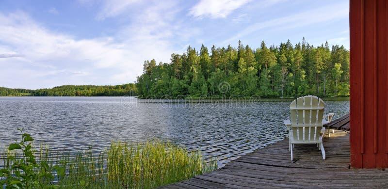 Trädgårds- stol bredvid en sjö fotografering för bildbyråer