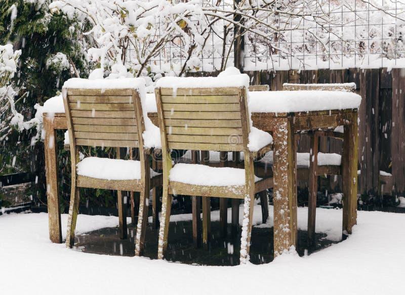 Trädgårds- tabell och stolar under snö arkivbilder