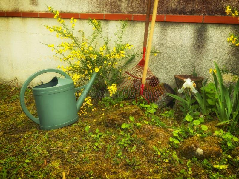 Trädgårds- tillbehör i trädgården nära väggen av huset arkivbilder