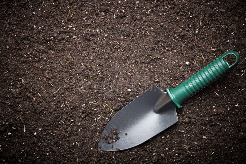 Trädgårds- Trowel i svart smuts royaltyfri foto