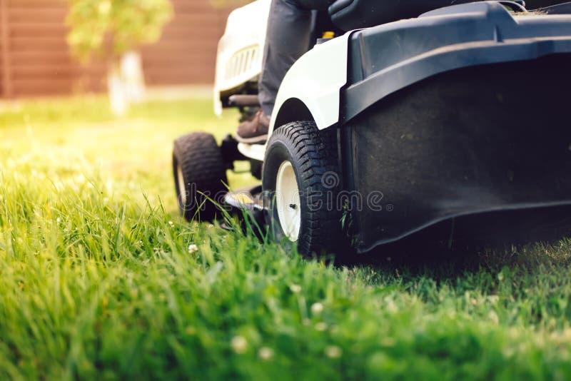 Trädgårds- underhåll - nära övre sikt av gräsgräsklippningsmaskinen royaltyfria foton