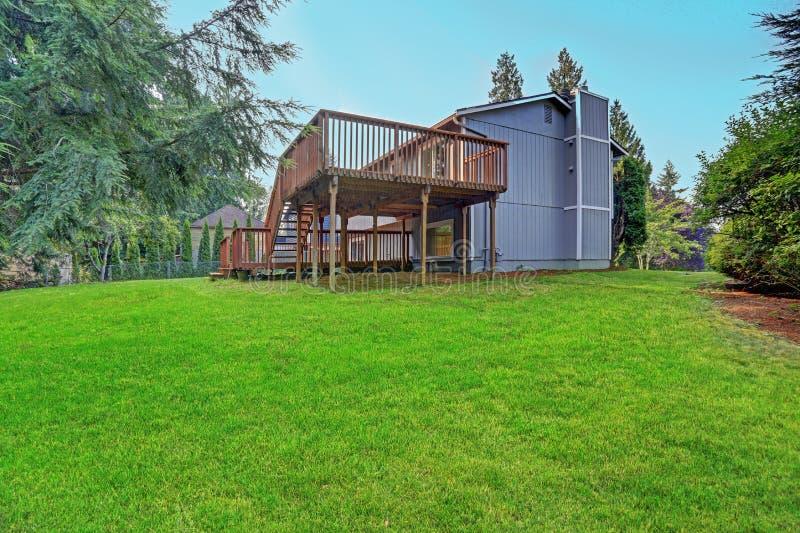 Trädgårdsikt av det gråa vandrarehuset med övre- och lägre däck arkivfoton