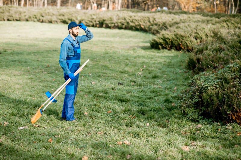 Trädgårdsmästare med rengörande hjälpmedel i trädgården arkivfoto