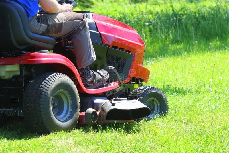 Trädgårdsmästare som kör en ridninggräsklippare i en trädgård arkivbilder