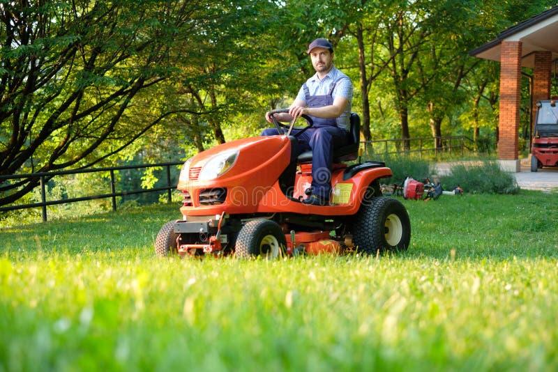 Trädgårdsmästare som kör en ridninggräsklippare i trädgård fotografering för bildbyråer