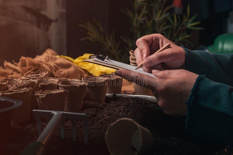 Trädgårdsmästarehandstilanmärkningar på skrivplattaanmärkningspapper royaltyfri bild