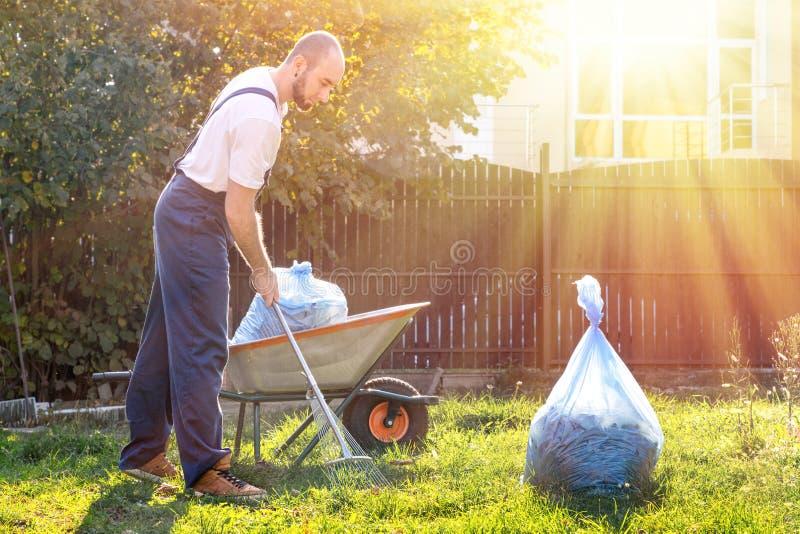 Trädgårdsmästaren i den blåa likformign gör ren gården På gräset är en vagn med kompost och en packe av avskräde brigha arkivbild