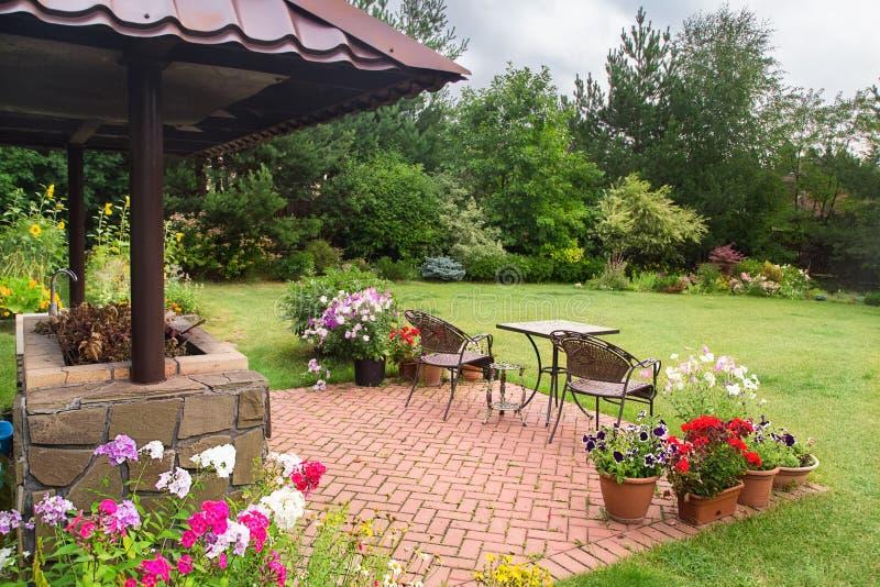 Trädgårduteplatsområde med spisen och möblemang Miljöpartietområde arkivfoton