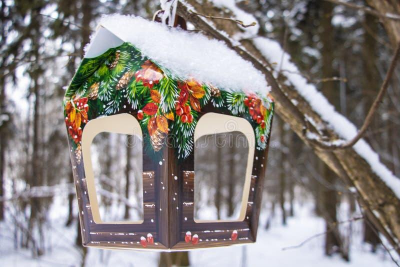 trädhus för fåglarna, gladlynta apartmen En färgrik hemlagad fågelförlagematare på trädet Vinterfågelförlagemataren i parkerar, s arkivfoton