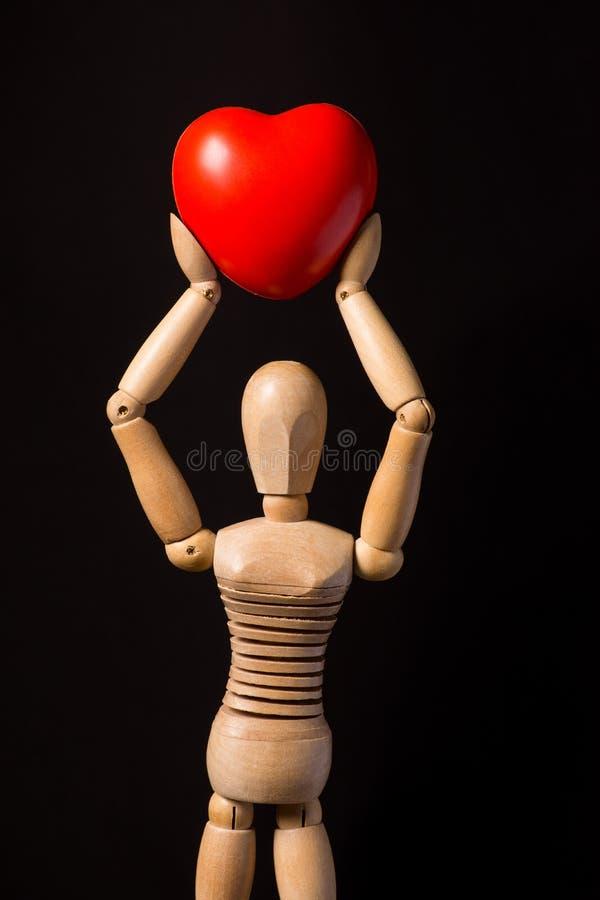 Trädocka med en röd hjärta i hans händer på en svart backgroun royaltyfria foton