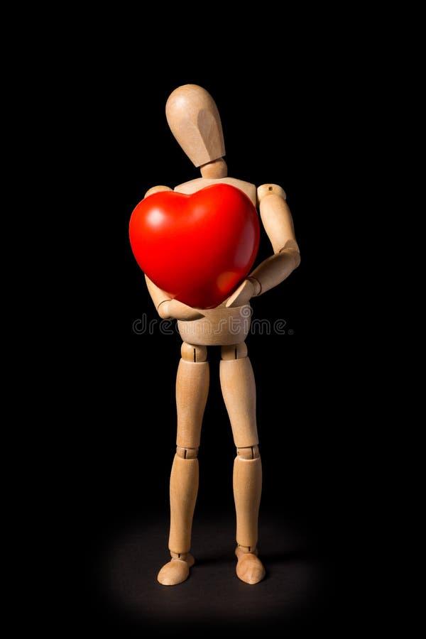 Trädocka med en röd hjärta i hans händer på en svart backgroun arkivbilder