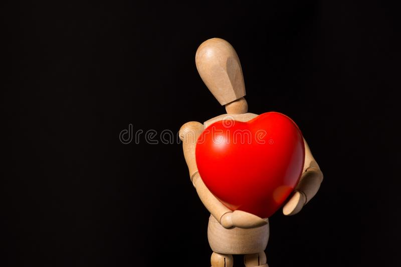 Trädocka med en röd hjärta i hans händer på en svart bakgrund fotografering för bildbyråer