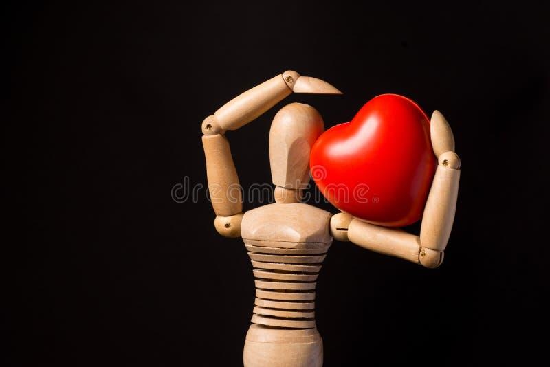 Trädocka med en röd hjärta i hans händer på en svart bakgrund royaltyfria foton