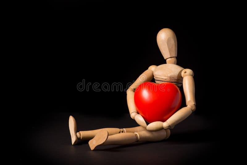 Trädocka med en röd hjärta i hans händer på en svart bakgrund arkivbild