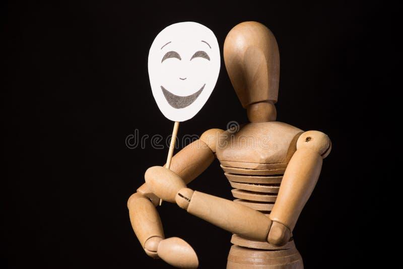 Trädockan på gångjärn rymmer en maskering i händer och täcker hennes framsida på en svart bakgrund royaltyfri fotografi