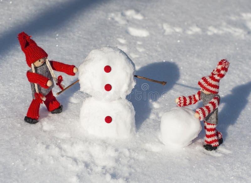 Trädockor i röd stucken kläder rullar kastar snöboll ner till buil royaltyfri bild