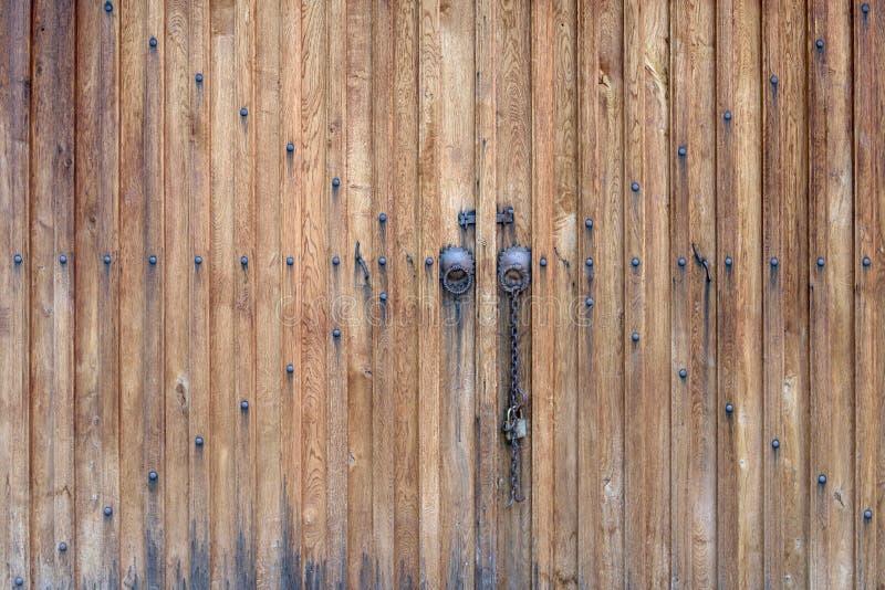Trädubbel dörr med metallhandtag och en kedja arkivbilder