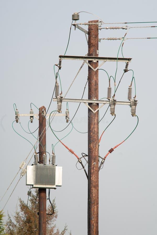 Träelektricitetspoler med trådar, isolatorer och transformatorn arkivfoto