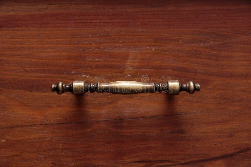 Träenheter av en gammal garderob med brons handtag arkivbild