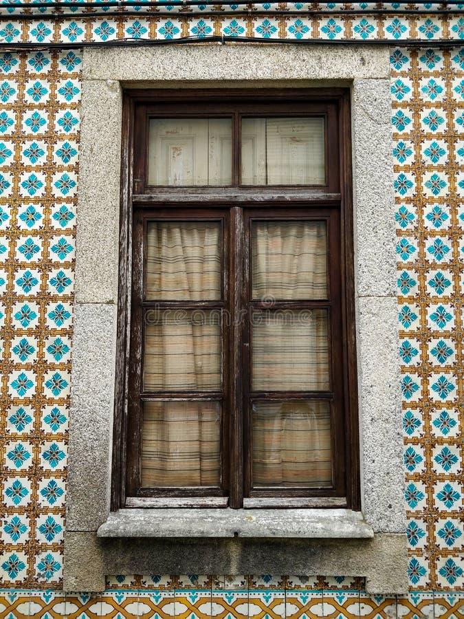 Träfönster av typiska portugisiska hus, med keramiska tegelplattor på fasaden royaltyfria foton