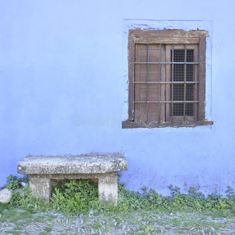 Träfönster och en liten stenbänk arkivbild