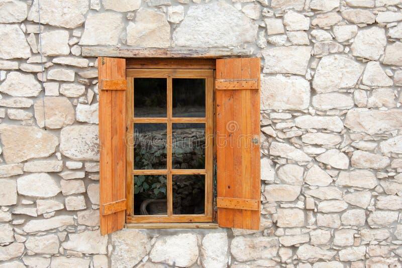 Träfönster och slutare i stenvägg royaltyfri foto