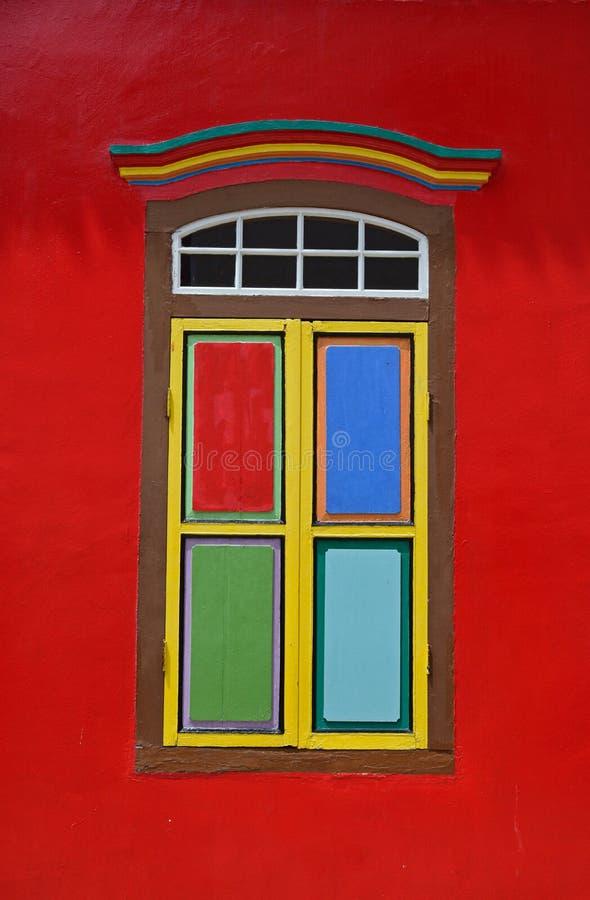 Träfönstret med bladdörrar stängde sig på den ljusa röda baserade väggen royaltyfria bilder