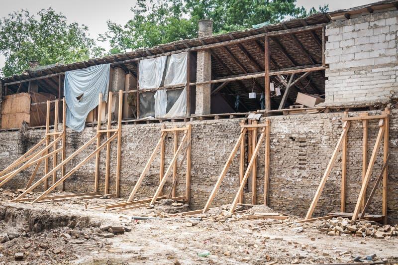 Träförstärkningstrålar som rymmer den gamla tegelstenväggen av det förstörda och skadade huset, kollapsade i den naturliga jordsk arkivbild